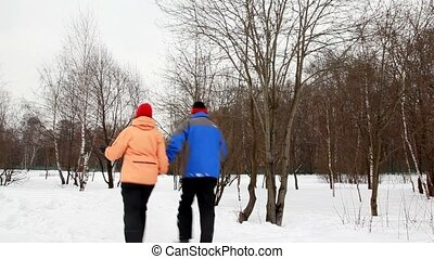man and woman run on snow aside winter birch forest, then back