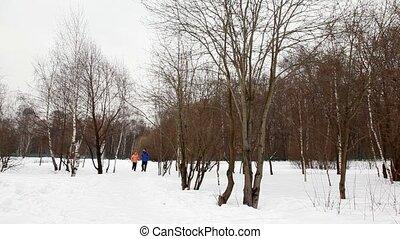 man and woman run on snow from winter birch forest