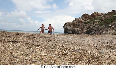 man and woman run out of the sea