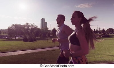man and woman running in city park - A man and a woman are...