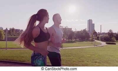 man and woman running in city park - Sporty couple running...