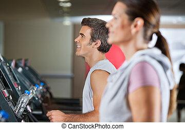 Man And Woman Running On Treadmill