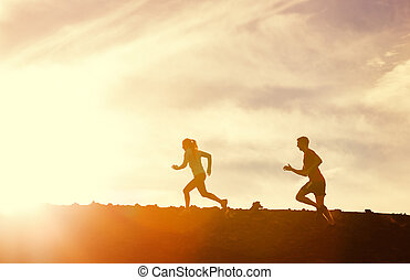 Man and woman running together into sunset - Silhouette of...