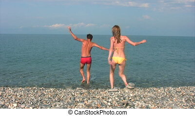 man and woman runs into sea and swims