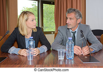 Man and woman sat at conference desk