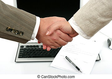 man and woman shaking hands in front of computer and...