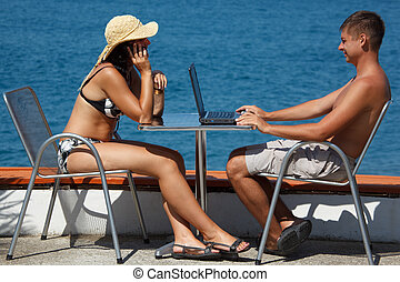 Man and woman sitting at table under open sky on background of sea. Man works for laptop. Girl talking on the phone.
