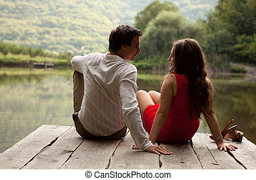 Man and woman sitting looking at each other while sitting on the wooden bridge over the lake