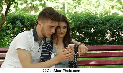 man and woman sitting on a bench and watching the pictures on phone