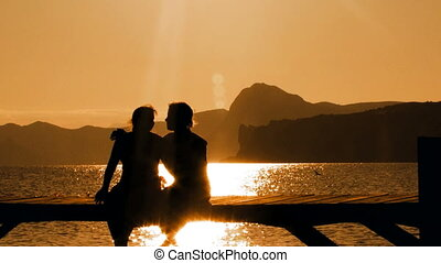 Man and Woman Sitting On Bridge At Sunset