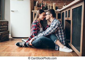 Man and woman sitting on kitchen floor and hugs