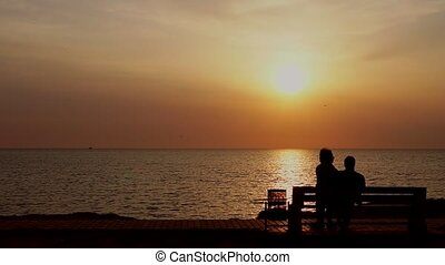 man and woman sitting on the bench watching the sunset on the sea
