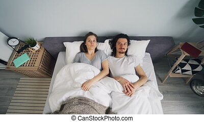 Man and woman sleeping in bed then waking up and rushing...