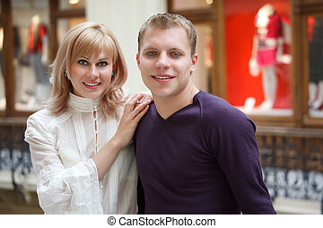Man and woman smiling looking at camera on background windows.