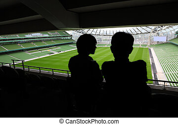 man and woman standing and talking on stadium, rows of...