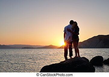 Man and woman standing in an embrace and watch the sunset -...