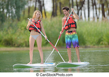 Man and woman standing on boards in river