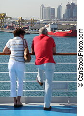 man and woman standing on deck of cruise ship and looking at port. man and woman in out of focus.