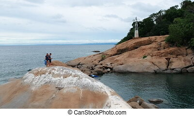 Man and Woman Standing on Island Rock Controlling Drone