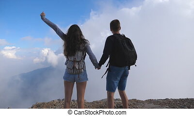 Man and woman standing on the edge of beautiful canyon, victoriously outstretching arms up. Young couple of tourists with backpacks reaching up top of mountain and raised hands. Rear view Slow motion