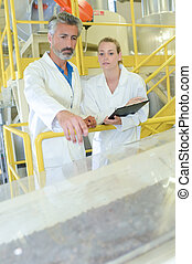 Man and woman stood on gangway observing factory