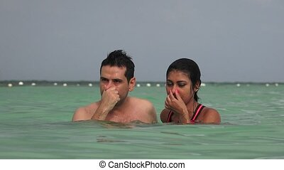 Man And Woman Swimming In Ocean And Talking