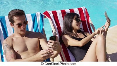 Man and woman taking self portraits at pool