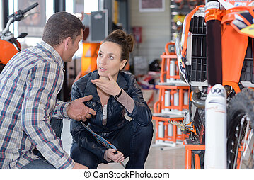 man and woman talking about motorcycle mechanic at the garage