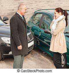 Man and woman talking after car crash