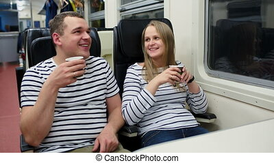 Man and woman talking and drinking tea or coffee in the train