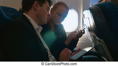Man and woman talking on business using pad