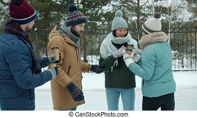 Man and woman are talking when friends are bringing them take out coffee at skating rink in winter. Recreational activities and friendship concept.