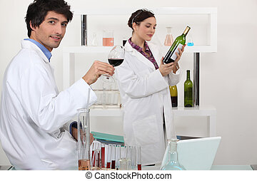 Man and woman testing wine in science laboratory