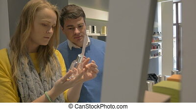 Man and Woman Trying Fragrances in Perfumery Shop - Man and...