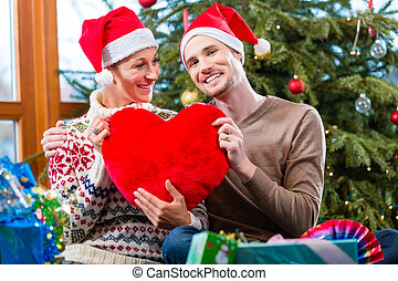 Man and woman under Christmas tree with presents