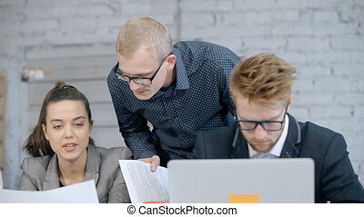 Man and woman using laptop and talking in office - Concept...