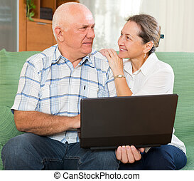 man and woman using laptop at home