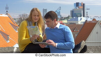 Man and woman using pad and map in city