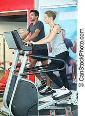 man and woman using step machines in fitness center