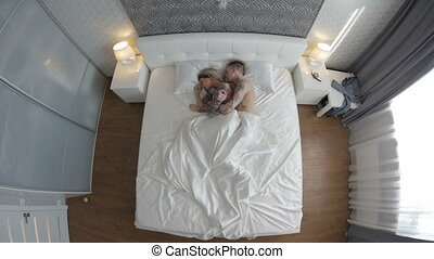 Man and woman wake up in the morning in their room. top view