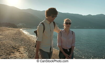 Man and woman walking along beach in warm weather.