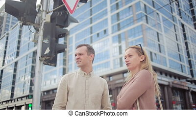man and woman walking on city street. onlookers stand at the crossroads
