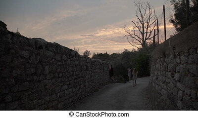 man and woman walking on the street during sunset. in the mountains