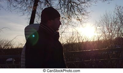 Man and woman walking together on a small bridge against sun in winter. 4K steadicam shot, profile view
