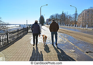 Man and woman walking with dog in the town