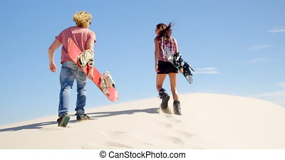 Man and woman walking with sand boards in the deserts 4k