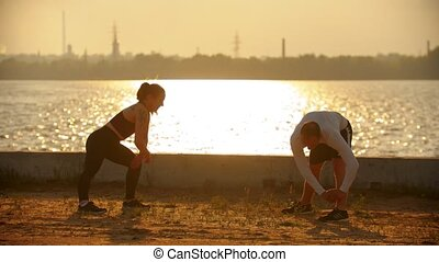 Man and woman warm up before the main load - Mid shot during...