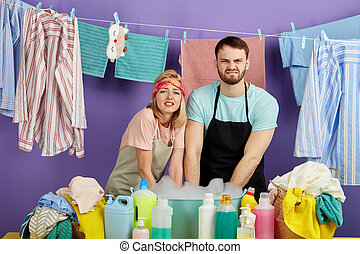 man and woman washing dirty clothes in the bowl with foam