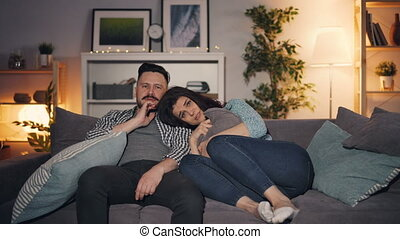 Man and woman watching shocking news on TV at home, guy...