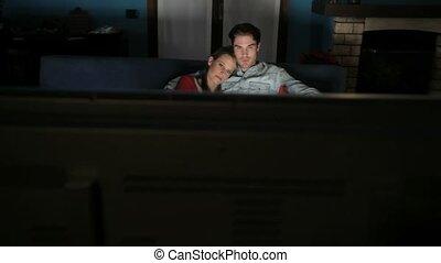Man and woman watching TV at home